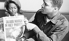 Muhammad Ali (right) holds a newspaper and poin...