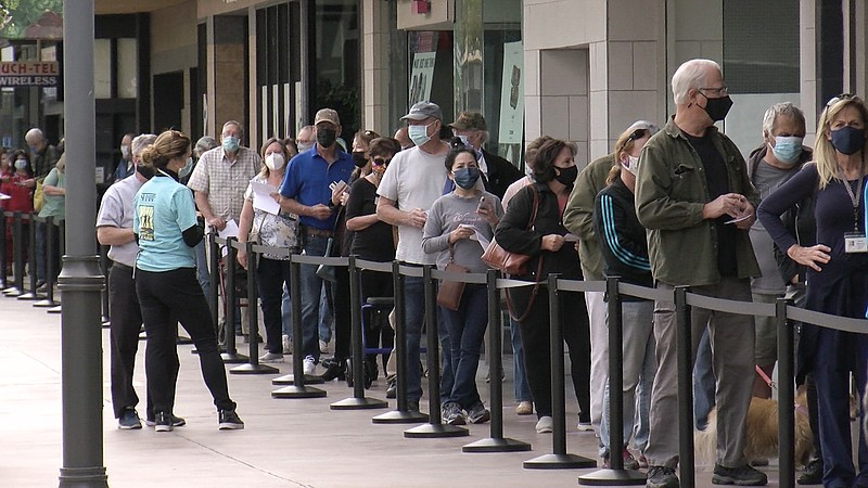 People wait in line for COVID-19 vaccines at the vaccination super station at...