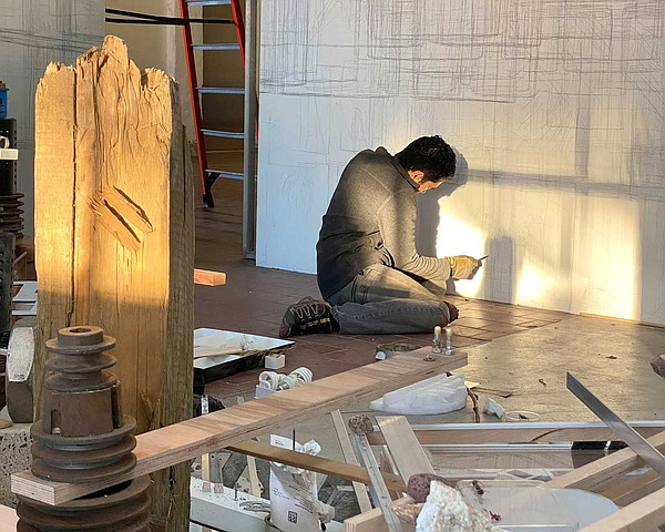 Artist Joshua Moreno is pictured at work on one of the si...