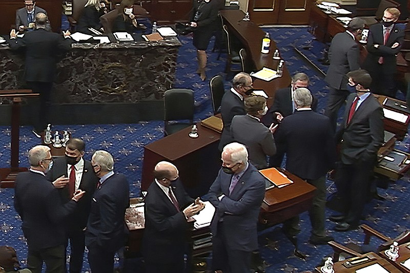 In this image from video, Republican senators and staff talk on the floor aft...