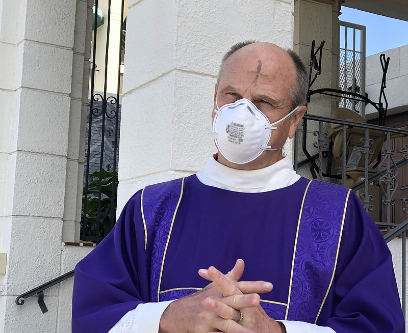 Deacon Dave Warren wears an N95 surgical mask with the mark of the ashen cros...