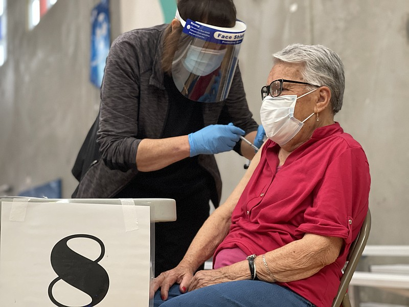 A patient gets vaccinated against COVID-19 at Border View Family YMCA in Otay...