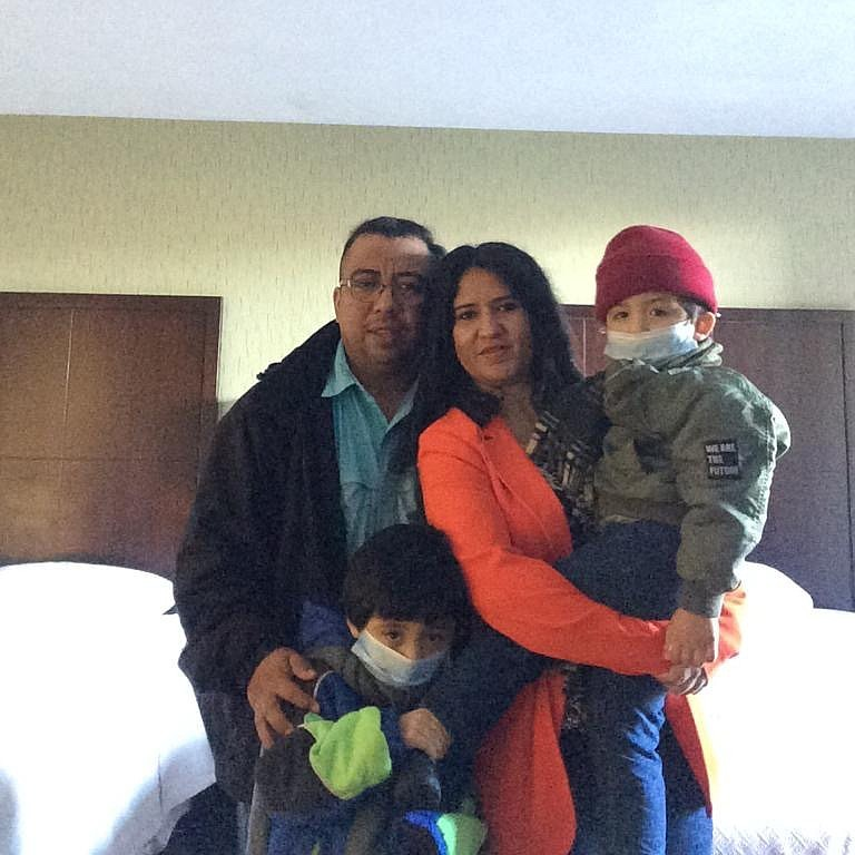 Gerson Eduardo Cano and his family pose for a photo in a San Diego hotel, sho...