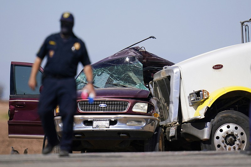 Law enforcement officers work at the scene of a deadly crash in Holtville, Ca...