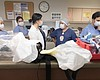Health care providers gather at the nurses' sta...