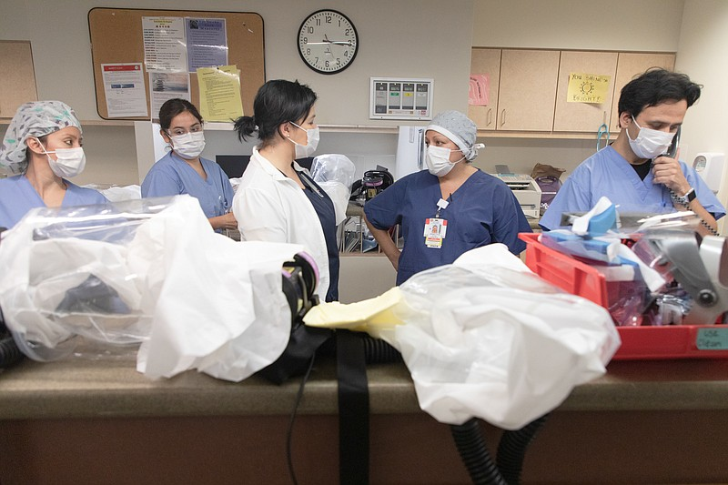 Health care providers gather at the nurses' station in the intensive care uni...