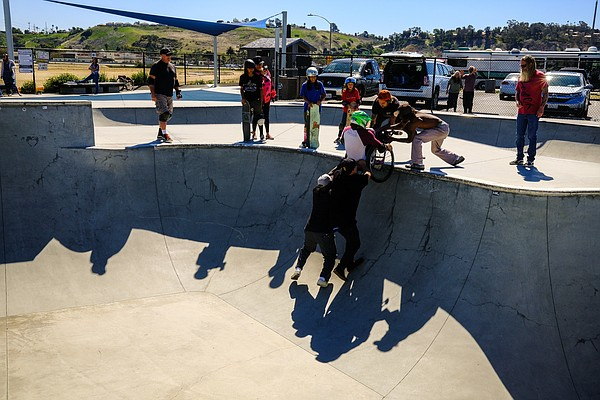 Skateboarders helping Tony Thogmartin out of a skating bo...