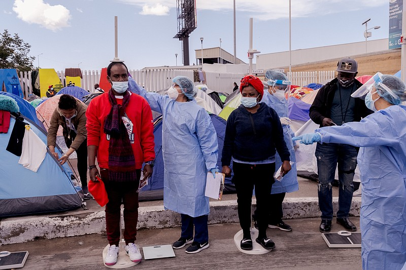 Health care workers from the city of Tijuana give migrants basic medical exam...