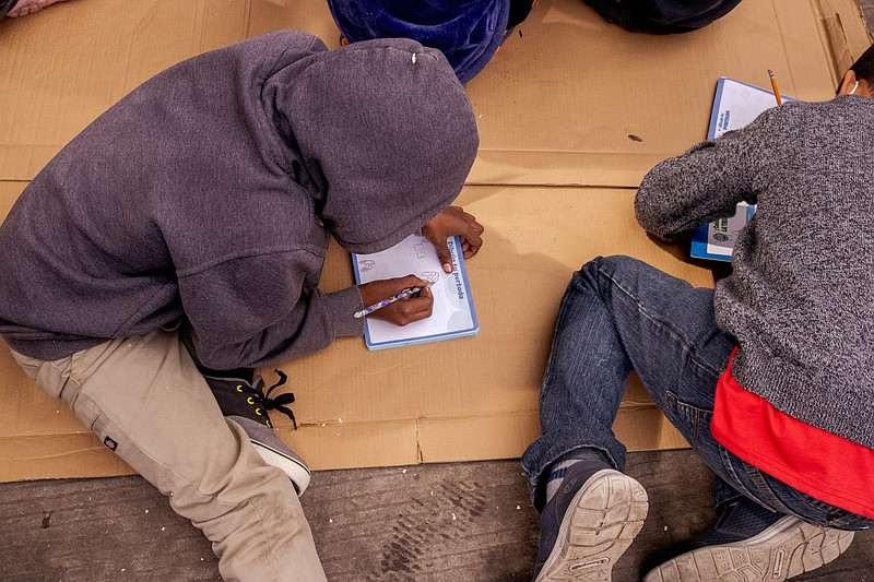Students do school work on the ground at a school started by asylum seekers f...