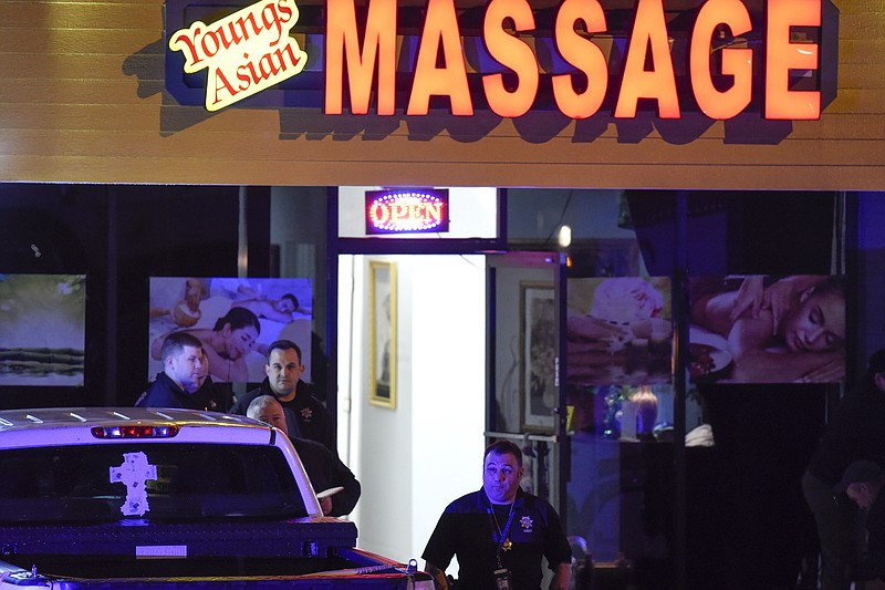 Authorities investigate a fatal shooting at a massage parlor, late Tuesday, M...