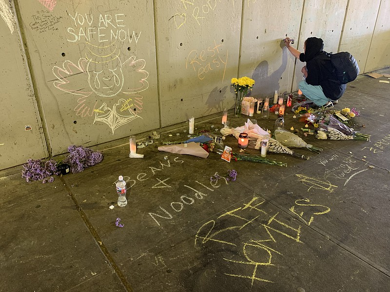 A woman writes a message on the wall of a tunnel where three homeless people ...