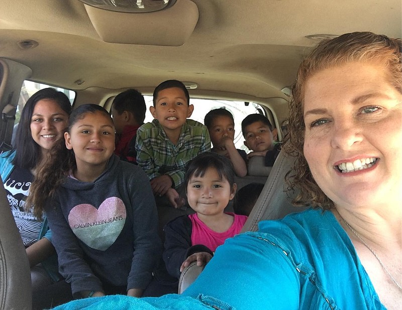 Danya Gresham (right) takes a selfie with some of the kids she helps take car...