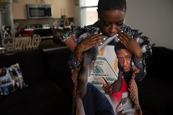 Maraston, who is holding a blanket with photos of her son...