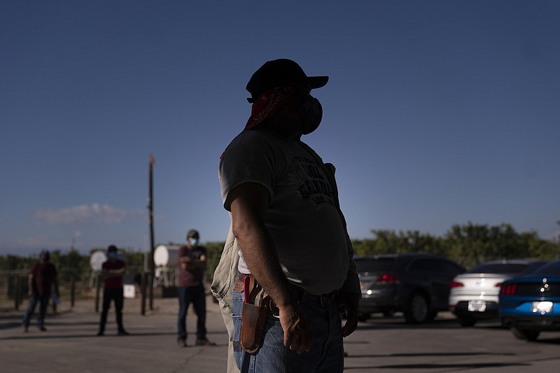 Hispanic farm workers wait in line to receive the Pfizer COVID-19 vaccine in ...