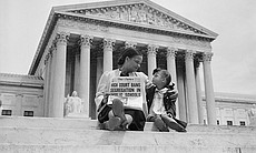A woman with child holds a newspaper up with th...