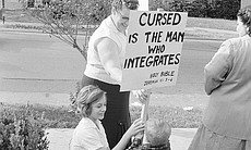 White women and child hold up a sign in support...