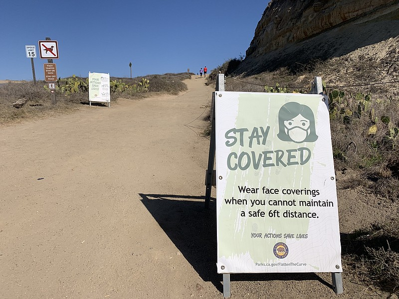 A sign warning people to wear masks due to COVID-19 at Torrey Pines State Bea...