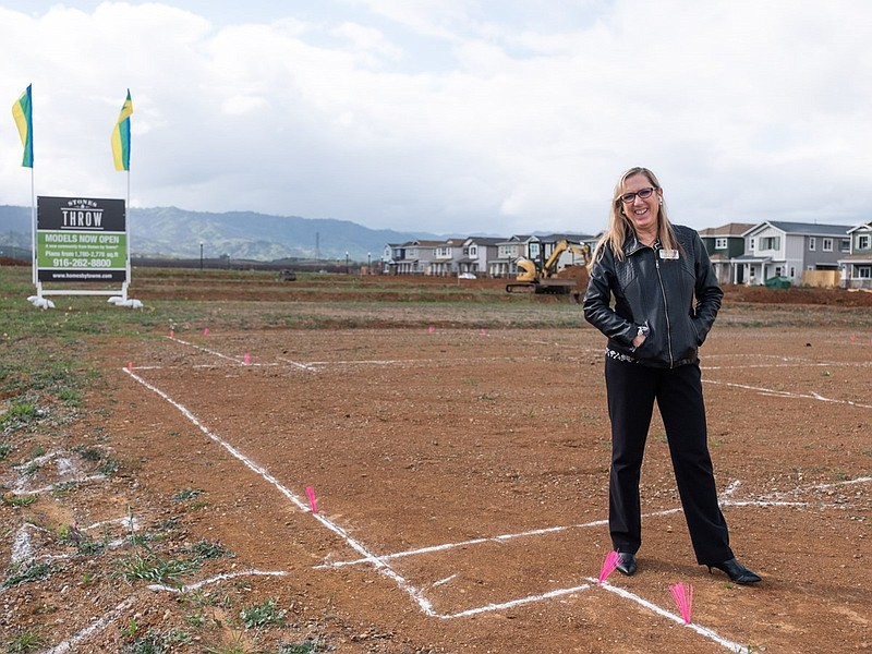 Laura Pope, sales consultant for Homes By Towne stands where homes will be bu...