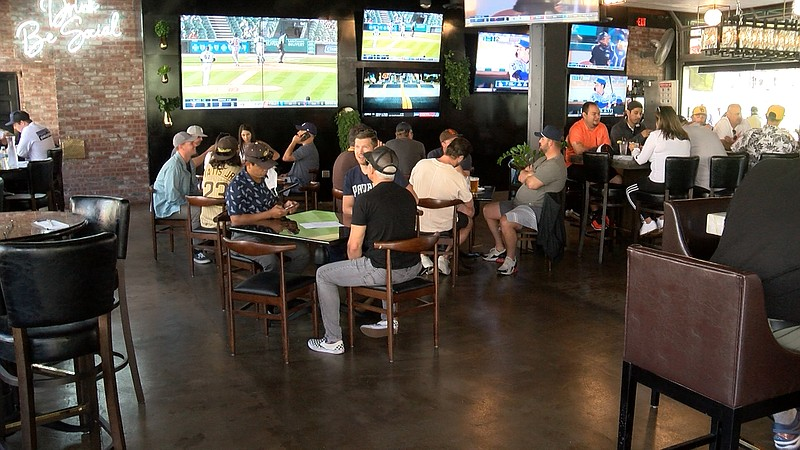 Guests sit at tables inside of Social Tap, a restaurant with a patio inside o...