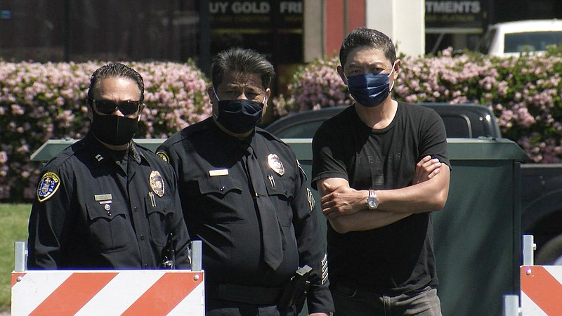 Two San Diego Police officers stand outside a parking lot next to business ow...
