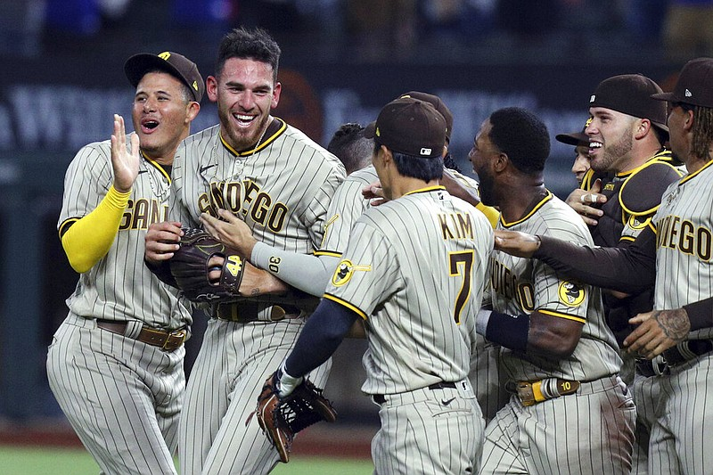 San Diego Padres starting pitcher Joe Musgrove, second from left, is mobbed b...