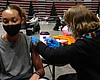 A young woman getting vaccinated against COVID-...