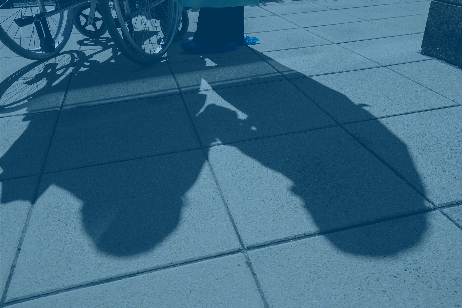 The shadow of a person in a wheelchair and their caregiver is pictured in thi...