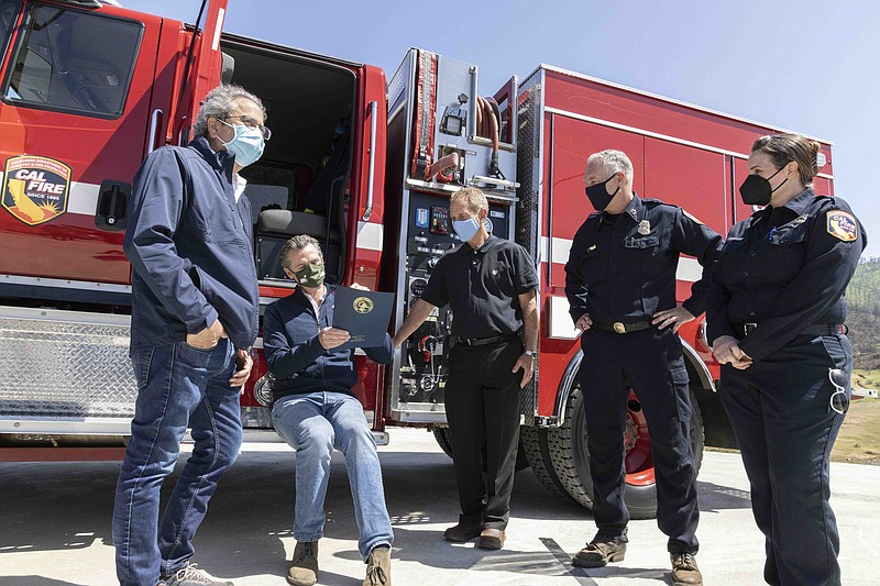 Gov. Gavin Newsom next to state and county fire officials signs a $536 millio...