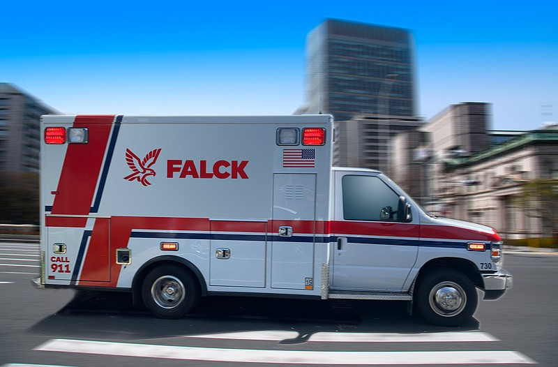 A Falck ambulance is showing driving on a street during the daytime in this u...