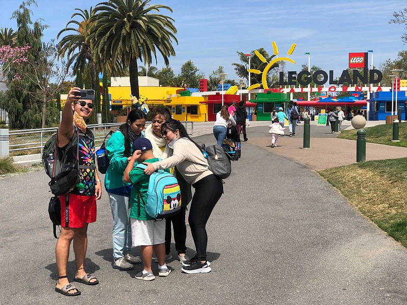 A family takes a photograph of themselves in front of the Legoland California...