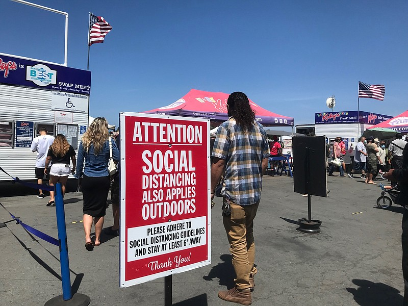 A sign outside the entrance of Kobey's Swap Meet at the Sports Arena encourag...