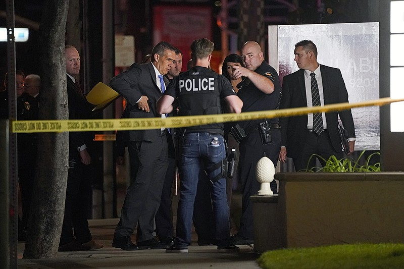 Investigators gather outside an office building where a shooting occurred in ...