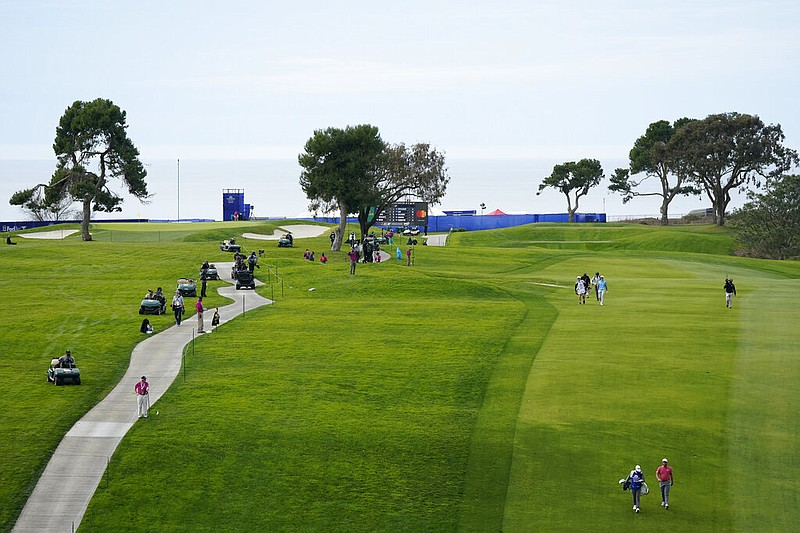 Jon Rahm, of Spain, lower right, walks down with 13th fairway with his caddy,...