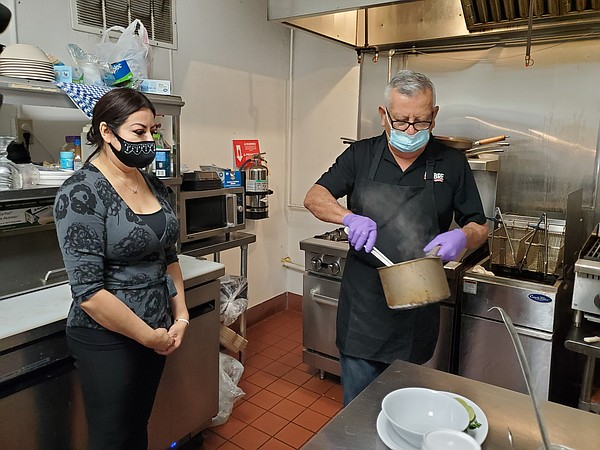 Tania Corona and her father work in the kitchen at their ...
