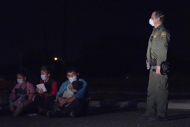 In this March 24, 2021 photo, a migrant man, center, holds a child as he look...