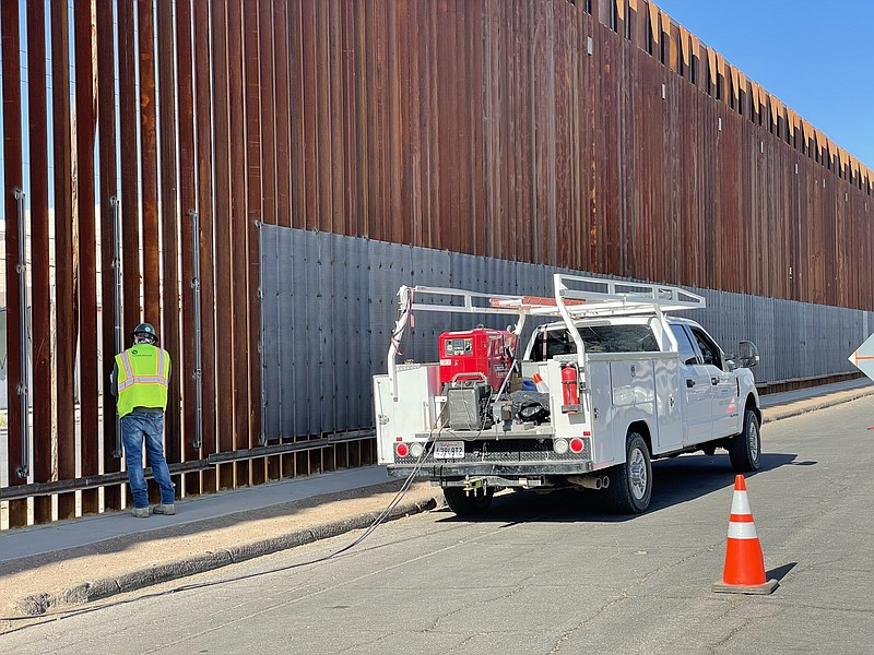 Worker is pictured welding sheets of metal onto the border wall in Calexico o...