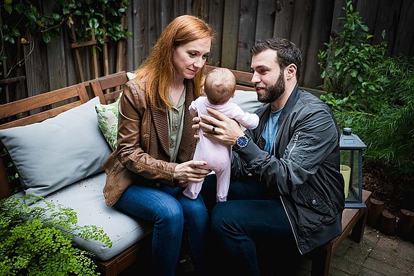 New parents, Erin and Gary Levin, gently play with their ...