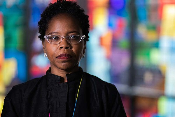 Reverend Stacey Edwards-Dunn stands in front of a stained...