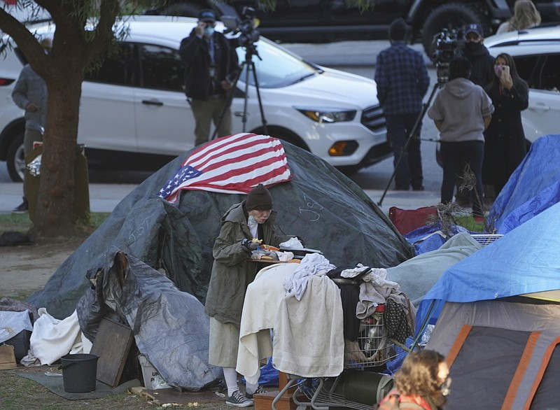 In this March 24, 2021, file photo a woman eats at her tent at the Echo Park ...