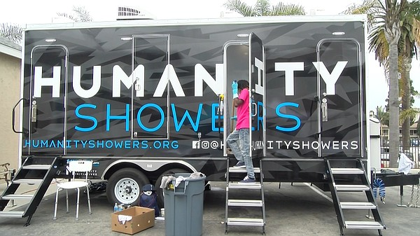 A volunteer sanitizes a shower stall from the Humanity Sh...