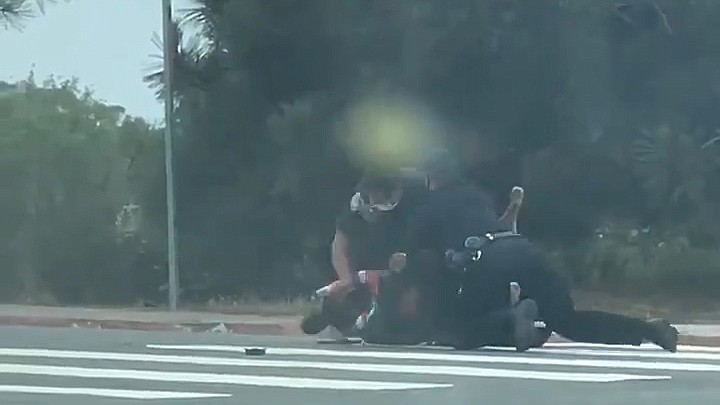 Still from a cell phone video showing a San Diego Police officer punching a h...