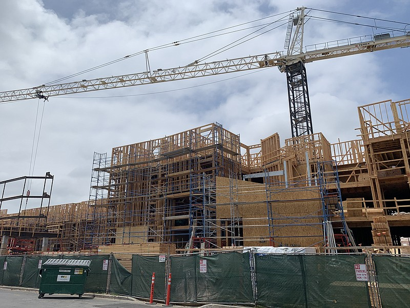 A crane towers over the wood framing of an apartment building under construct...