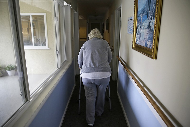 In this Dec. 5, 2019, file photo, a woman walks to her room at a senior care ...
