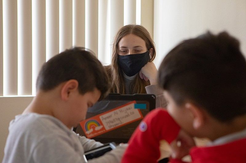 From her El Cajon home, Alaa Taha checks in on school assignments for one of ...