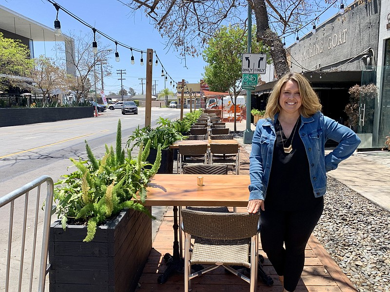 Tammy Piehl stands in the outdoor dining space set up on street parking space...