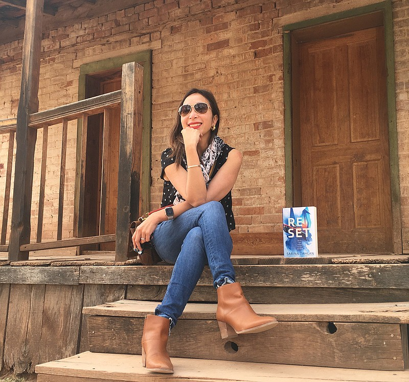 Author Sarina Dahlan is pictured with her book,