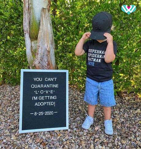 Pictured a young boy with a sign that reads,