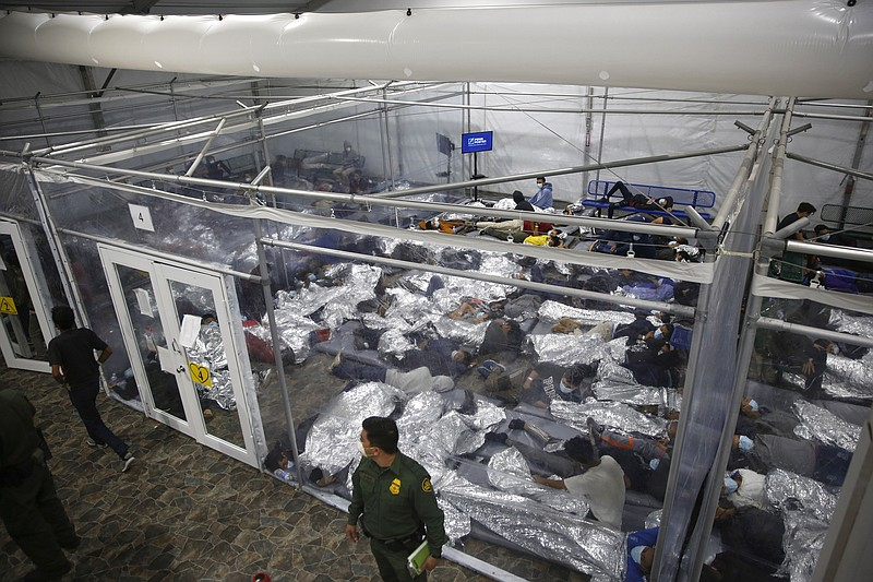 In this March 30, 2021, file photo, minors lie inside a pod at the Donna Depa...
