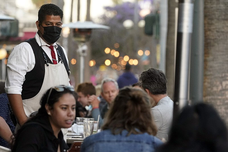 A server tends to customers in an outdoor dining area amid the COVID-19 pande...