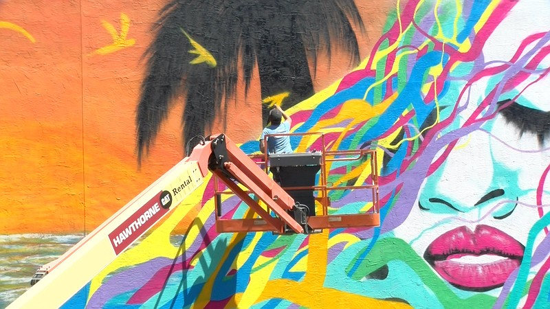 Mauro Alvarez, a local artist, stands on a lift and paints a bird on a mural ...